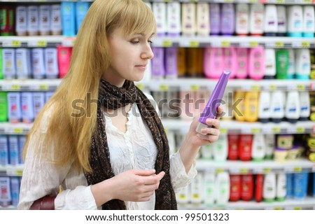 Blonde girl wearing white shirt chooses shampoo in large store; shallow depth of field - stock photo