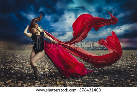 blonde girl with a huge red cloth in the wind, warrior and freedom - stock photo