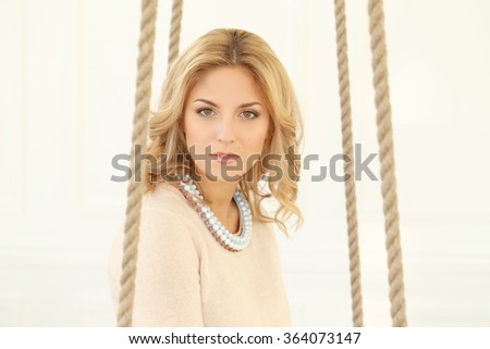 Blonde girl with curly hair sitting on the swing - stock photo