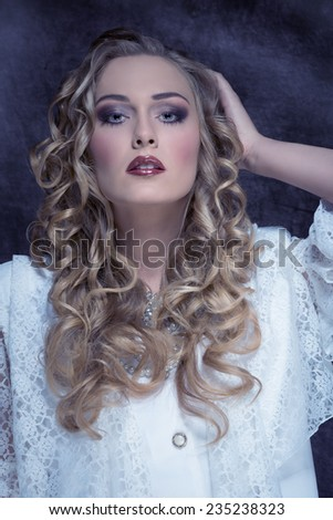 blonde girl with stylish make-up and long curly hair wearing retro lace elegant white clothes, precious jewellery and looking in camera  - stock photo