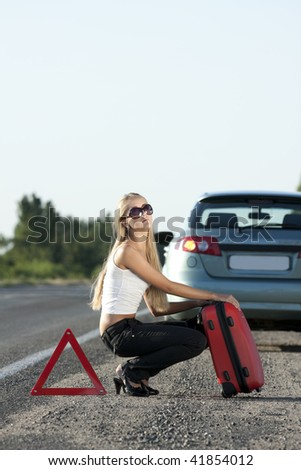 blonde girl with suitcase on the road - stock photo