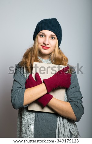blonde girl with the book in hand, the concept of Christmas and New Year, studio photo isolated on a gray background - stock photo