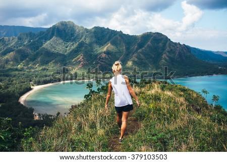 Blonde hiker looks over the ocean on a classic Hawaiian hike. - stock photo