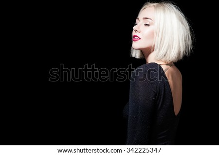 Blonde in a black dress with an open back on a black background - stock photo