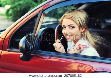Blonde in the car. Young woman with lipstick in the car   - stock photo