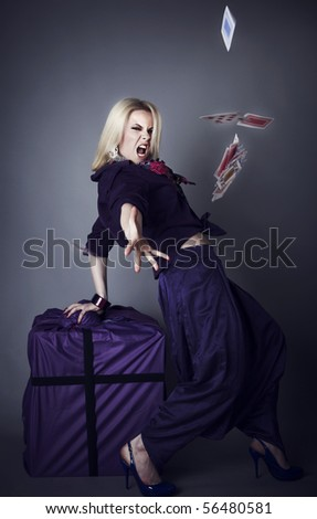 blonde in violet on a grey background scatters playing cards. Photo. - stock photo