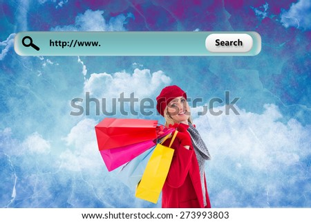 Blonde in winter clothes holding shopping bags against painted sky - stock photo