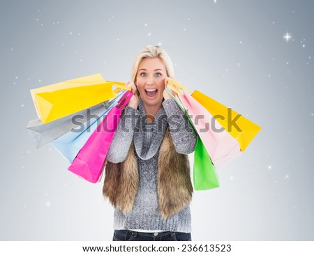Blonde in winter clothes holding shopping bags on vignette background - stock photo