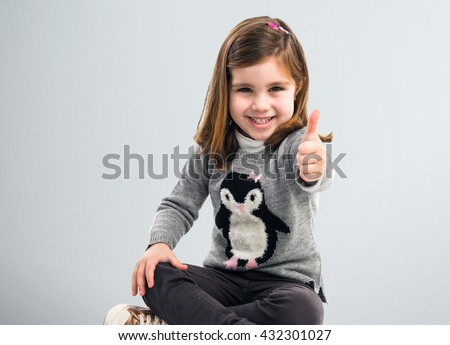 Blonde kid with thumb up over grey background - stock photo