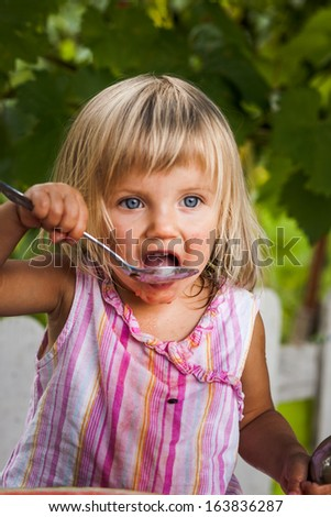blonde litle girl eats a slice of watermelon - stock photo