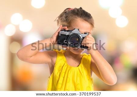 Blonde little girl photographing something on unfocused background - stock photo