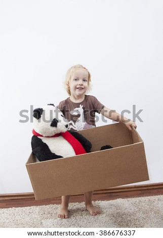 blonde little girl ready to move-with panda bear - stock photo
