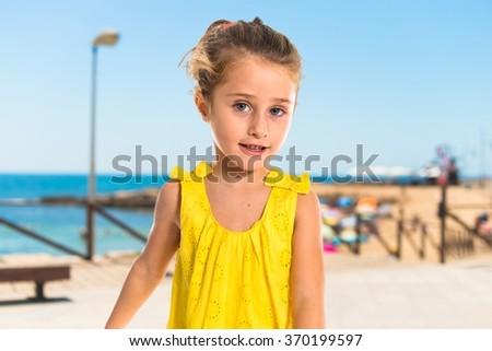 Blonde little girl walking on unfocused background - stock photo