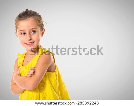 Blonde little girl walking with her arms crossed - stock photo