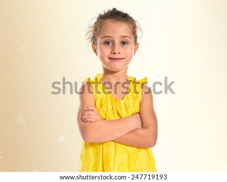 Blonde little girl with her arms crossed - stock photo