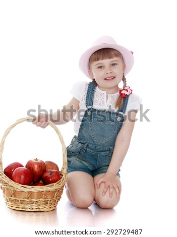 Blonde little girl with short braids in pink hats and overalls gathered a large basket of ripe apples - isolated on white background - stock photo