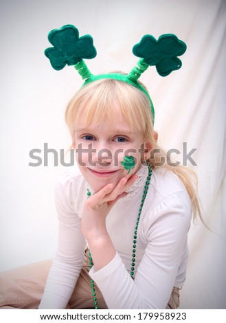 Blonde little girl with the Saint Patric's day symbols: clover leaf and green hat - stock photo