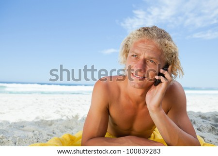 Blonde man lying on his beach towel while talking on his mobile phone - stock photo