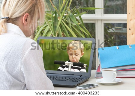 Blonde middle aged woman is communicating with a angry blond boy standing on the scooter. She is communicating by a notebook computer. - stock photo