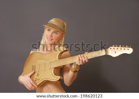 Blonde Model Playing golden Guitar while smiling. - stock photo