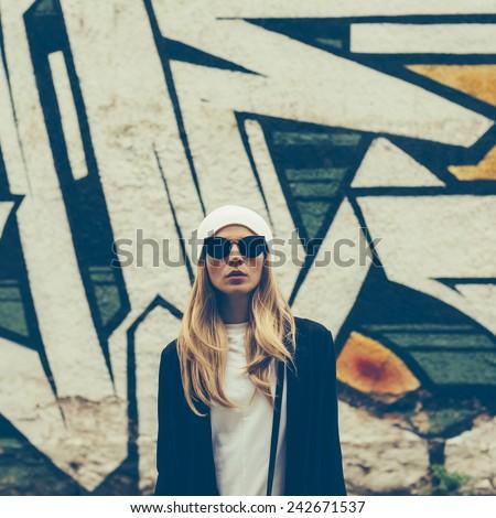 blonde on city street. Trendy urban Look. Cap and stylish Sunglasses. - stock photo