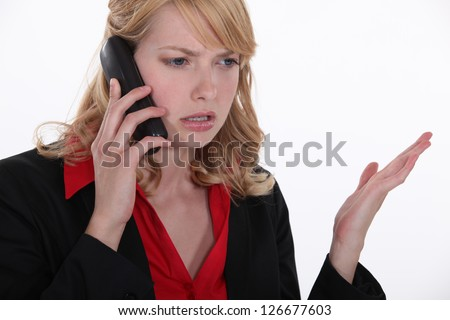 blonde on the phone looking annoyed - stock photo