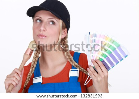 blonde painter looking inspired holding color chart and brush - stock photo