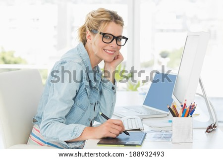 Blonde pretty designer looking at the camera using digitizer in creative office - stock photo