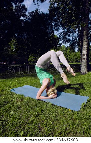 blonde real girl doing yoga in green park, gymnastic head over hills - stock photo