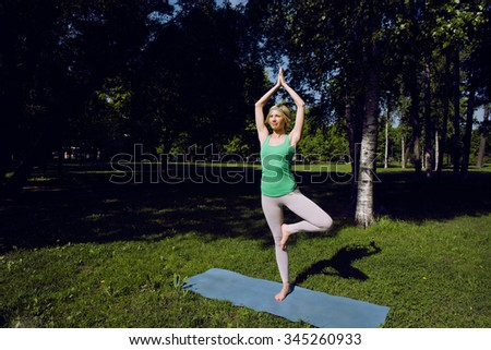 blonde real girl doing yoga in green park, gymnastic head over hills outside - stock photo