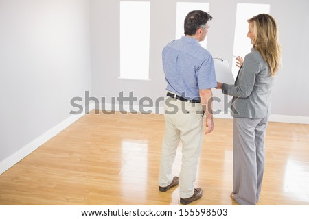 Blonde realtor showing an empty room and some documents to a potential mature buyer - stock photo