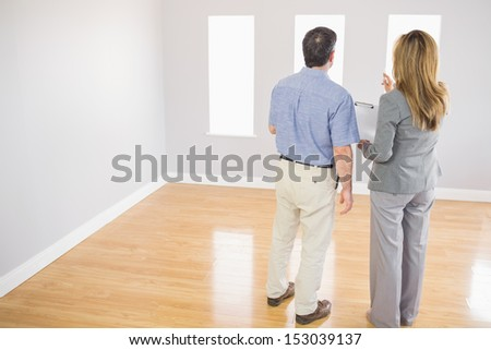 Blonde realtor showing an empty room to a potential mature buyer - stock photo