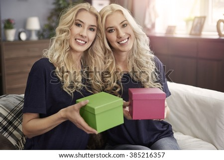 Blonde sisters holding two small gift  - stock photo