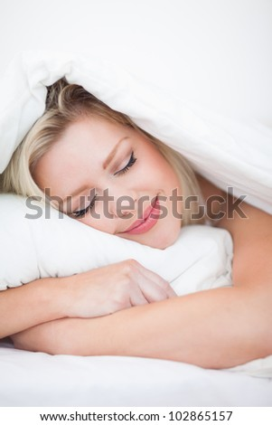 Blonde sleeping peacefully in her bed - stock photo
