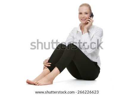blonde smiling businesswoman seated on the floor and using mobile phone - stock photo