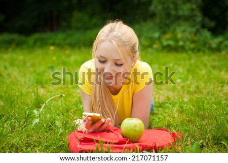 blonde smiling girl holding cell phone and listening music with white headphones - stock photo