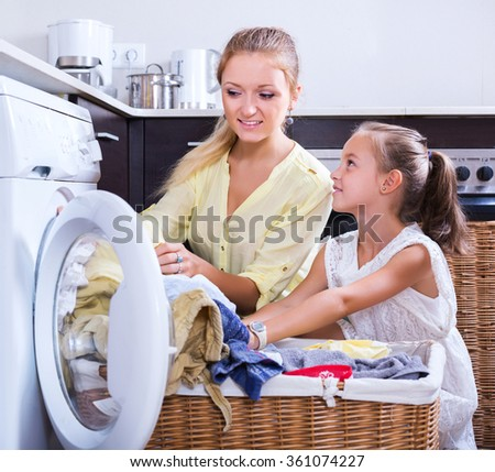 Blonde smiling housewife and little girl doing laundry together at home - stock photo