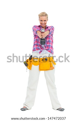 Blonde standing while pointing a drill at camera on white background - stock photo