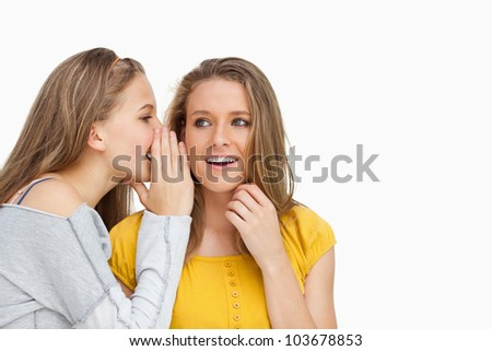 Blonde student whispering to her beautiful friend against white background - stock photo