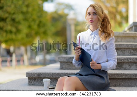 Blonde student with blue eyes in school uniform. Cute School Girl sitting outside after classes or test exams   - stock photo