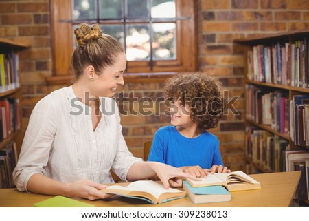 Blonde teacher and pupil reading books in the library in school - stock photo