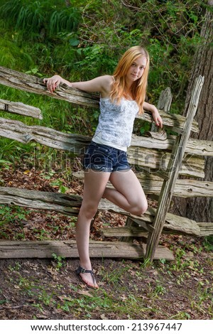 Blonde teen girl leaning against a wood fence - stock photo