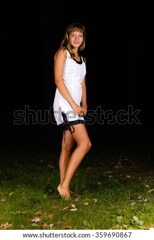 blonde teenage girl standing on the grass - stock photo