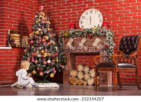 Blonde toddler boy playing near Christmas tree - stock photo