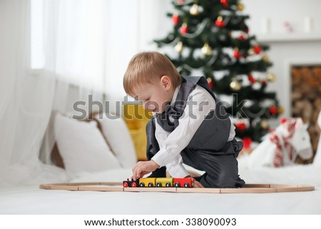Blonde toddler boy playing near Christmas tree - stock photo