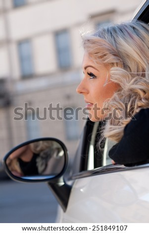 blonde tourist watches something from her car, she's blonde and beautiful and she may have spotted something amazing - stock photo