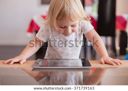 blonde two years old baby white shirt smiling happy face reading and watching digital tablet on wood and crystal table indoor at home - stock photo