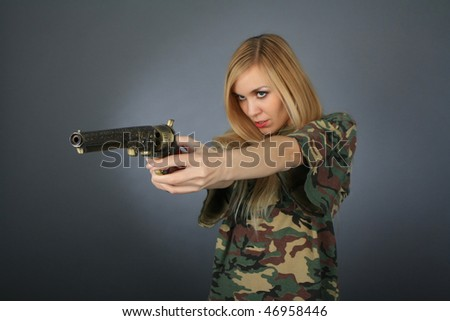 Blonde with a revolver focusing on a revolver - stock photo