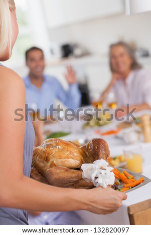 Blonde woman bringing thanksgiving turkey to the dinner table - stock photo