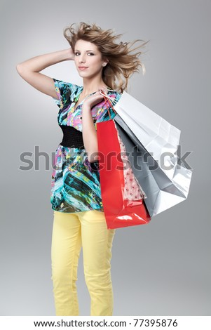 blonde woman carrying shopping bags wind hair - stock photo